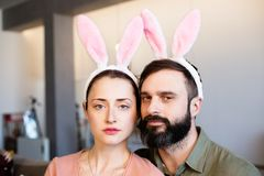 Funny couple wearing bunny ears and having fun at Easter day. Funny couple wearing bunny ears and having fun at Easter day stock photography