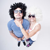 Funny couple wearing wigs fighting (comic concept of fight) Stock Photography