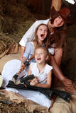 Funny cowgirls. Three beautiful girl with long healthy hair in hats sitting on hayloft in cowboy clothes on a horse farm royalty free stock images