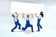 Funny craftsmen lifiting a heavy commercial board. Funny, young craftsmen lifiting a heavy commercial board stock images