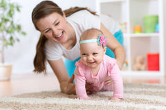 Funny crawling baby girl with mother. At home Stock Images