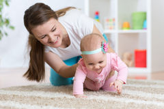 Funny crawling baby girl with mother. In nursery Stock Photos