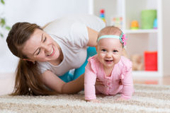 Funny crawling baby girl with mother Royalty Free Stock Photos