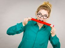 Business woman biting pencil. Funny crazy business woman wearing eyeglasses biting pencil. Studio shot on grey background royalty free stock photography
