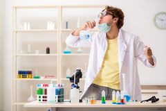 The funny crazy chemist doing experiments and tests royalty free stock photography