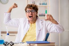 The funny crazy chemist doing experiments and tests stock photo