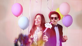 Funny crazy couple having awesome time dancing. In party photo booth, graded stock video footage
