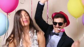 Funny crazy couple having fun in photo booth stock video