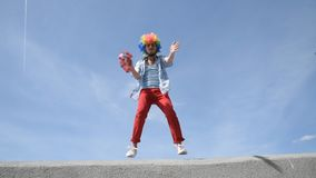 Crazy mime dance on the parapet with a tambourine against the sky. Funny clown antics. Funny and crazy dance and antics of a mime on a parapet with a tambourine stock video footage