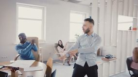 Funny crazy dancing businessman celebrating victory with excited multi-ethnic colleagues in modern light office 4K. Funny crazy dancing young businessman stock footage