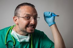 Funny crazy doctor holding a surgical knife Stock Photo