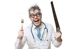 Funny and crazy doctor is laughing and holds saw in hand on whit Stock Photos