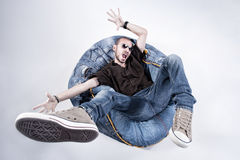 Funny crazy man dressed in jeans and sneakers. Standing on denim beanbag royalty free stock photography