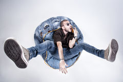 Funny crazy man dressed in jeans and sneakers. Standing on denim beanbag royalty free stock photo