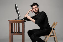 Funny and crazy man using a computer. On gray background. man's hand pointing at the monitor. Concept of surprise and indignation Royalty Free Stock Photos