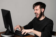 Funny and crazy man using a computer Stock Photography