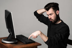 Funny and crazy man using a computer. On gray background. man's hands on the keyboard Royalty Free Stock Photo