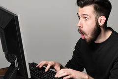 Funny and crazy man using a computer Stock Image