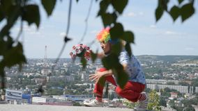 Crazy mime dancing on the parapet with a tambourine. Funny movement of a clown against the backdrop of the city. A funny and crazy mime is dancing with a stock video footage