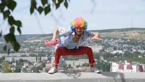 Crazy mime dancing on the parapet with a tambourine. Funny movement of a clown against the backdrop of the city. A funny and crazy mime is dancing with a stock footage