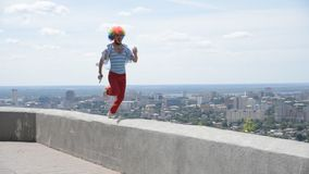 Crazy mime runs along the parapet with a pistol. A funny clown with a gun rushes against the background of the city. A funny and crazy mime is running with a stock footage