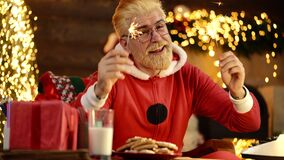Funny crazy Santa Claus with sparkles, bengal light. New Year Holiday. Positive human facial expressions and emotions
