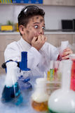 Funny crazy scientist boy working in a laboratory Royalty Free Stock Images