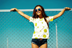 Funny crazy stylish model girl in the street in casual hipster summer cloth Stock Photos