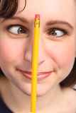 Funny cross eyes of woman with pencil on her nose Royalty Free Stock Photography