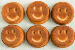 Funny homemade cupcakes in form of smiling face. Funny cupcakes in form of smiling face. Food that causes positive emotions. Humorous sweet food. Good mood Royalty Free Stock Images