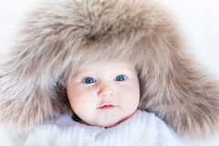 Funny curious baby girl in a huge winter hat Royalty Free Stock Photo