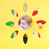Funny curly baby girl playing hide and seek. On playground Stock Images