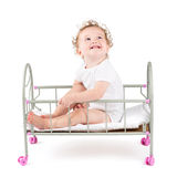 Funny curly baby paying in a doll bed Royalty Free Stock Photos