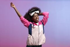 Funny curly brown-haired girl dressed in the pink sports jacket is wearing on her head the virtual reality glasses in stock photos