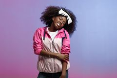 Funny curly brown-haired girl dressed in the pink sports jacket is wearing on her head the virtual reality glasses in. The studio on neon background stock images