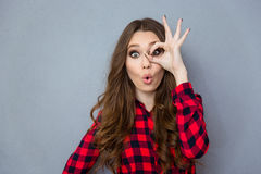 Funny curly girl showing okay gesture near her eye Royalty Free Stock Photos