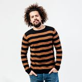 Funny curly guy with a beard dressed in a striped black and yellow sweater and jeans poses in the studio on the white royalty free stock photography