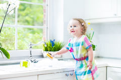 Funny curly toddler girl in colorful dress washing dishes. Cute curly toddler girl in a colorful dress washing dishes, cleaning with a sponge and playing with royalty free stock photos