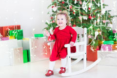 Funny curly toddler girl under a beautiful Christmas tree with presents. Funny curly toddler girl playing with a red bell in a white rocking chair under a stock image