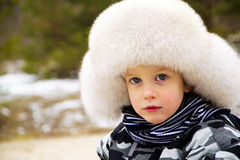 Funny cute baby boy wearing a huge winter hat Stock Photos