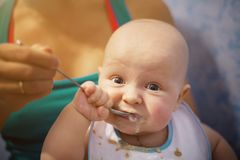 Funny and cute baby eats first meal in a spoon. A newborn boy is smeared with porridge, eats and looks into the camera royalty free stock images