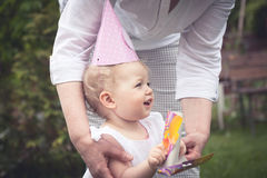 Funny cute baby girl in birthday cap playing with mother in park during birthday party Stock Image