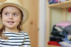 Funny baby girl is putting on hat at home royalty free stock images