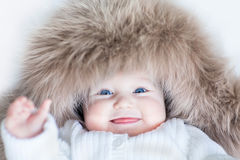Funny cute baby girl wearing huge winter hat. Funny cute baby girl with big blue eyes wearing a huge winter hat Stock Photo