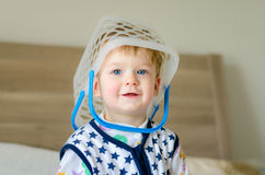 Funny cute baby kid with busket on head playing home Stock Photography