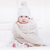 Funny cute baby wearing hat and huge knitted scarf stock photo