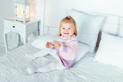 Funny and cute blond little laughing girl playing on bed Stock Photos