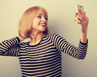Funny cute blond woman making self photo of herself haircut and Stock Photos