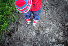 Funny cute boy looking onto own feet. Baby standing on saphalt in red shoes Royalty Free Stock Images