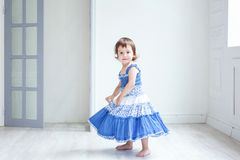 Little girl in bright room. Funny and cute brunette little smiling girl playing and dancing in bright room Royalty Free Stock Image